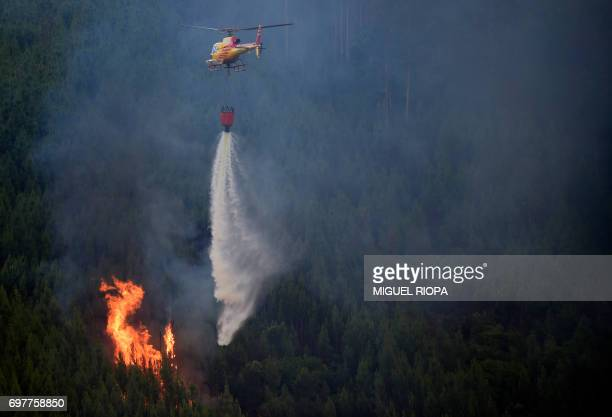 TOPSHOT A helicopter drops water over a wildfire in Carvalho next to Pampilhosa da Serra on June 19 2017 More than 1000 firefighters are still trying...