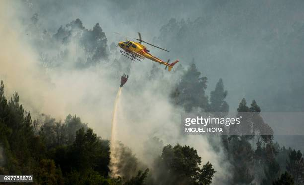 A helicopter drops water over a wildfire in Carvalho next to Pampilhosa da Serra on June 19 2017 More than 1000 firefighters are still trying to...