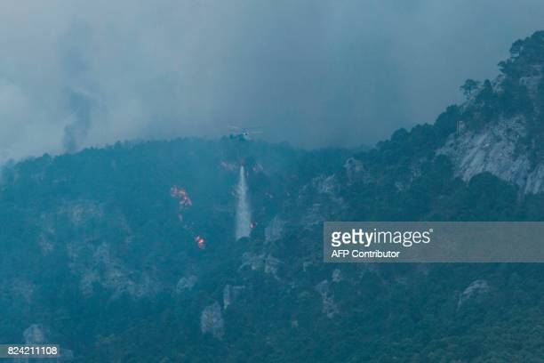 A helicopter dumps its payload over a wildfire in Cerro de Rala near Yeste in south eastern Spain on July 27 2017 Fires ravaged bone dry pine forests...