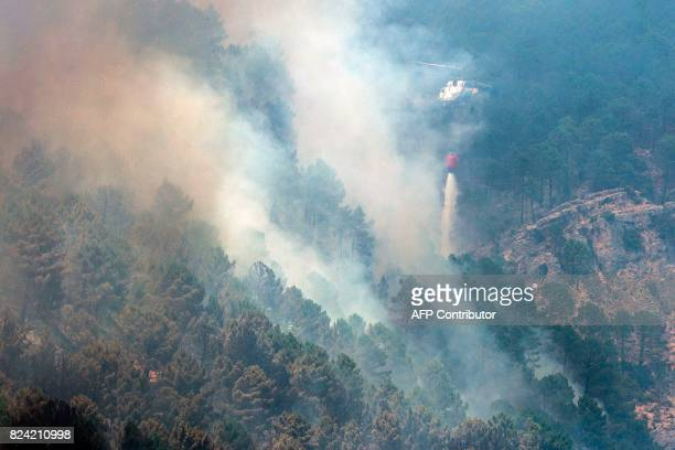 A helicopter dumps its payload over a wildfire near Yeste in south eastern Spain on July 27 2017 Fires ravaged bone dry pine forests and is still not...