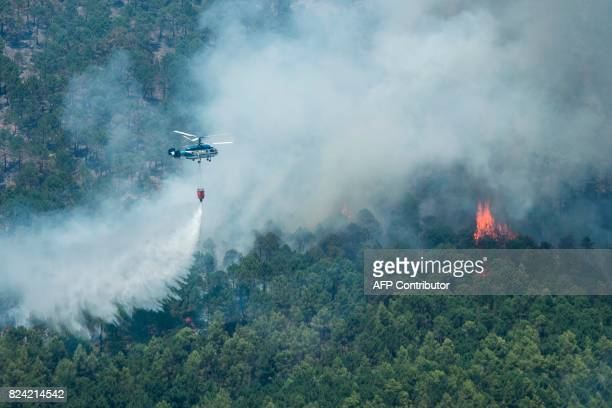 A helicopter dumps its payload over a wildfire near Yeste in south eastern Spain on July 28 2017 Fires ravaged bone dry pine forests and is still not...