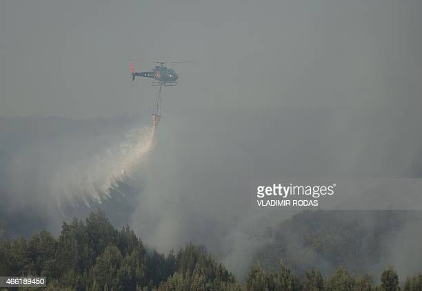 A helicopter fights the forest fire in the sector of Agua Santa in Valparaiso Chile on March 14 2015 Chile declared a state of emergency Friday and...