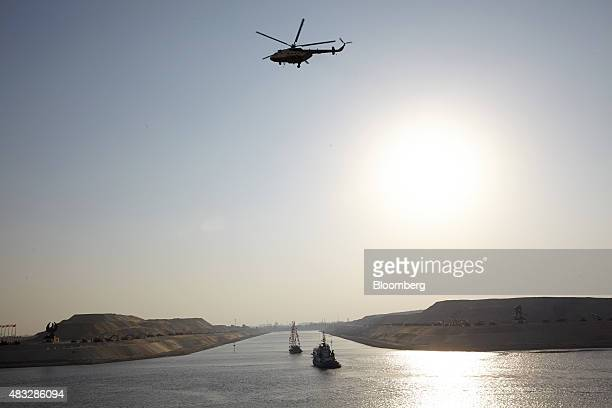 A helicopter flies above vessels entering a channel which joins the old canal to the New Suez Canal right operated by the Suez Canal Authority in...