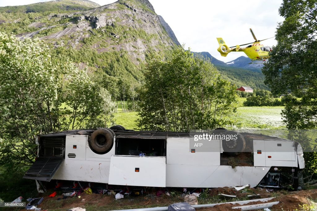 A helicopter flies near a crashed bus in Valldal near Geiranger on the south west coast of Norway on July 30 2016 One person was killed and several...
