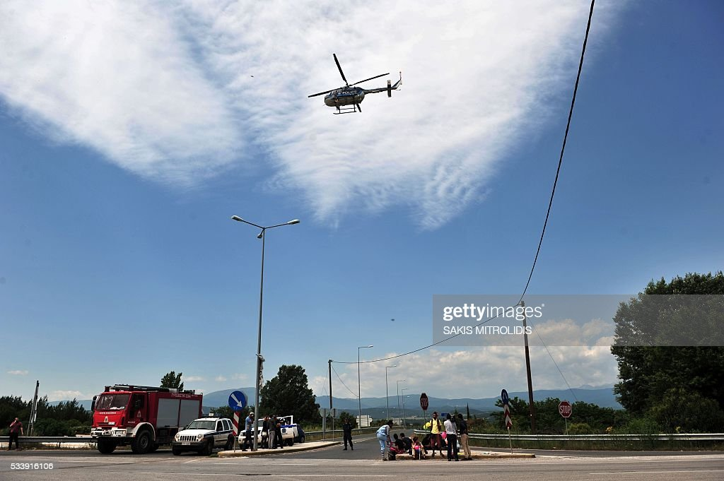 A helicopter flies near the makeshift camp at the Greek-Macedonian border, near the Greek village of Idomeni, on May 24, 2016, during its evacuation. Hundreds of Greek police on May 24 began clearing the overcrowded Idomeni camp, a migrant flashpoint on the Macedonia border where thousands have been living in squalid conditions for more than three months. Over 800 people were put on buses to newly-opened camps in the vicinity of Greece's second city Thessaloniki, about 80 kilometres (50 miles) to the south in an operation that began shortly after sunrise, police said. MITROLIDIS