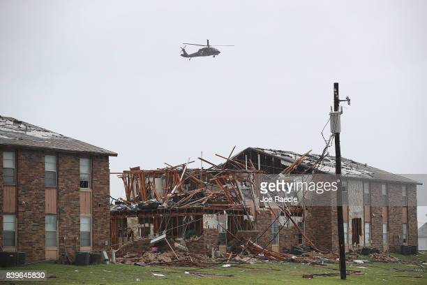A helicopter flies over a destroyed apartment complex after Hurricane Harvey passed through on August 26 2017 in Rockport Texas Harvey made landfall...