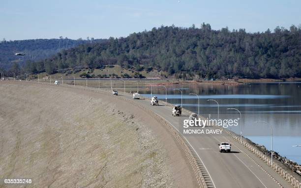 A helicopter flies over cement trucks on the top of the Oroville Dam in Oroville California on February 14 2017 A sheriff lifted a mandatory...