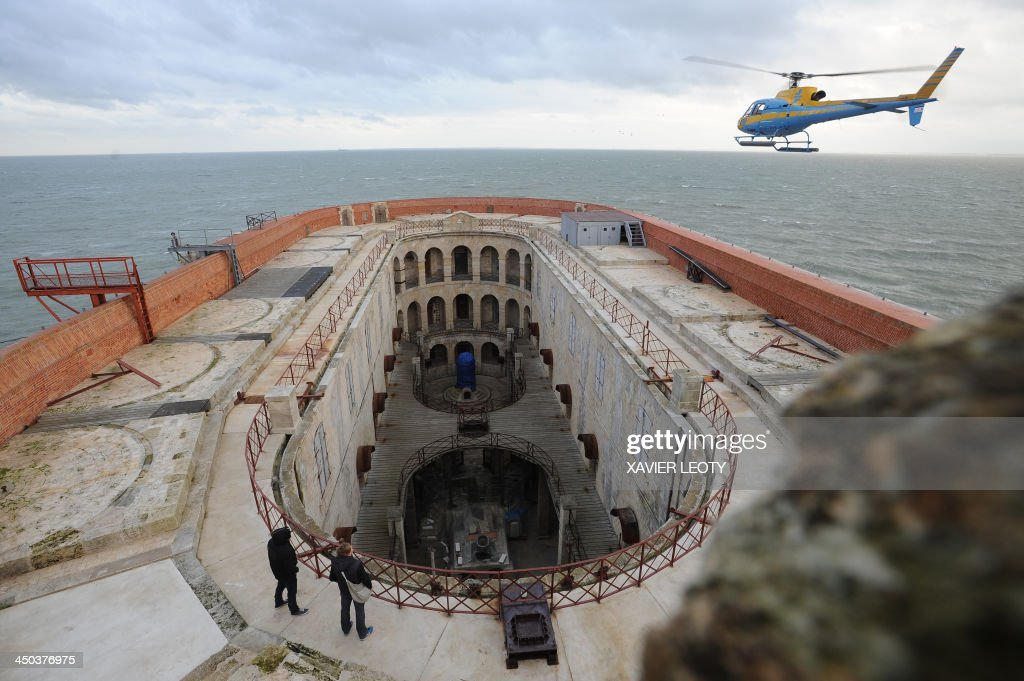 A helicopter flies over Fort Boyard, a fort in the Atlantic Ocean off the coast of France, near La Rochelle, on November 15, 2013. The fort is the filming location for the TV gameshow 'Fort Boyard' and is undergoing renovations. Workers arrive on Monday morning by helicopter and leave on Friday evening. During the winter the renovations are on hold and will pick up again in March 2014.