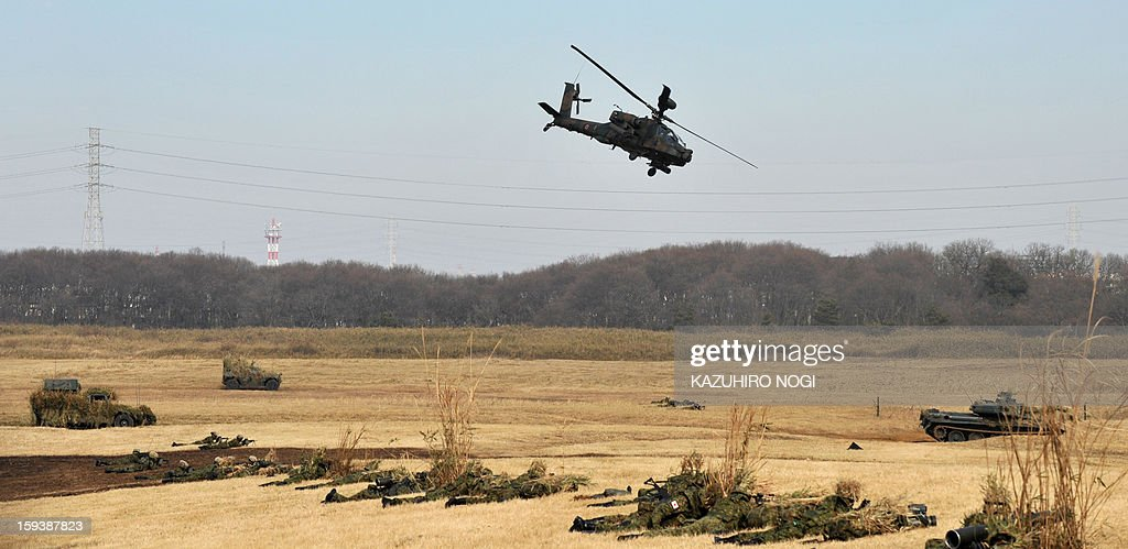 A helicopter flies over Japanese Self Defense Force ground troops participating in a new year military drill at the training grounds in Narashino, suburban Tokyo on January 13, 2013. A total of 300 personnel, 20 aircraft and 33 vehicles took part in the open exercise at the defense force's Narashino training ground. AFP PHOTO / KAZUHIRO NOGI