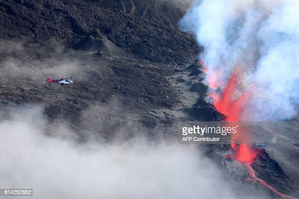 A helicopter flies overhead as lava errupts and flows from the Piton de la Fournaise the volcano of the French Indian Ocean island of Reunion which...