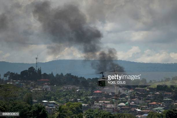 A helicopter flies through smoke billowing from houses after aerial bombings by Philippine Airforce planes on Islamist militant positions in Marawi...