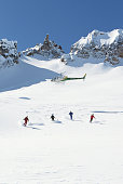 Helicopter Flying Above Skiers