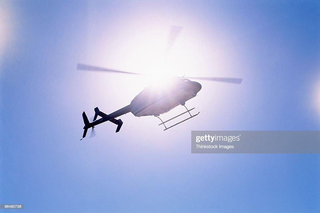 Helicopter flying by sun