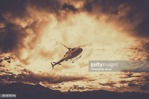 Helicopter Flying in Mountains With Dark Clouds