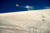 Helicopter flying over ski tracks from heli skiers