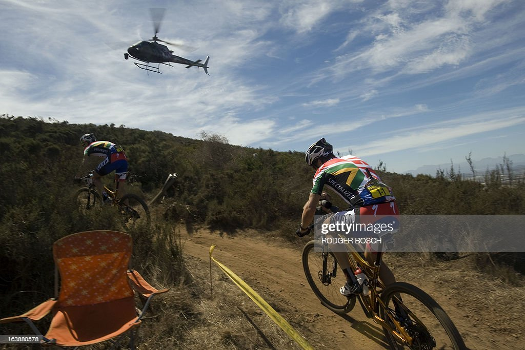 A helicopter follows Czech Olympic gold medalist Jaroslav Kulhavy on March 17, 2013 during the prolog stage of the 2013 Cape Epic Mountain Bike Race at the Meerendal Wine estate, about 30 kms from Cape Town. The eight-day race covers a distance of more than 800 kms, climbing more than 15,000 meters. AFP PHOTO / RODGER BOSCH