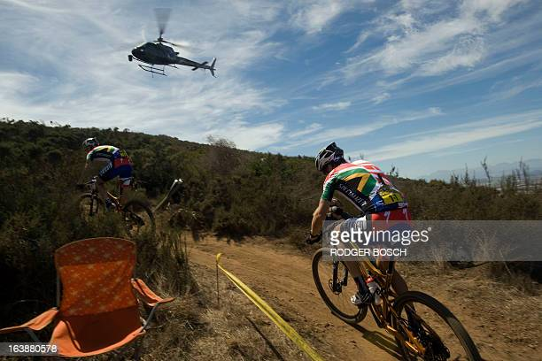 A helicopter follows Czech Olympic gold medalist Jaroslav Kulhavy on March 17 2013 during the prolog stage of the 2013 Cape Epic Mountain Bike Race...
