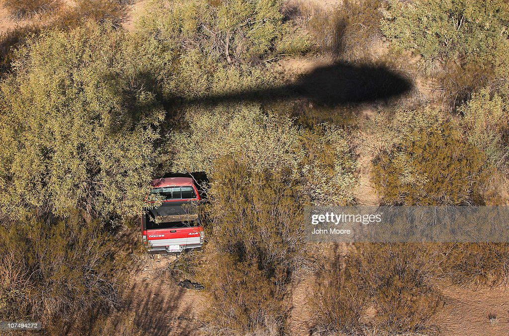 A helicopter from the U.S. Office of Air and Marine patrols over a discarded truck, that was likely used for drug smuggling, in the Sonoran Desert while searching for illegal immigrants and smugglers on December 9, 2010 in the Tohono O'odham Reservation, Arizona. The federal agency works closely with the U.S. Border Patrol in searching for smugglers and illegal immigrants who cross into the United States in remote areas all along the Mexican border.