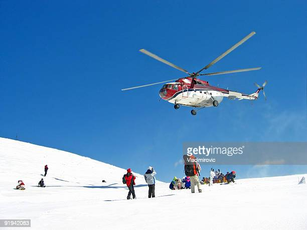 A helicopter hovering over a group of hikers on snow