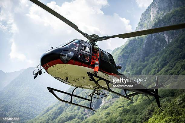 Helicopter hovers above grassy landing area