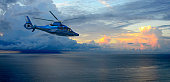 A helicopter flies by as Thunderstorms build over the Atlantic Ocean at sunrise in Palm Beach, Florida