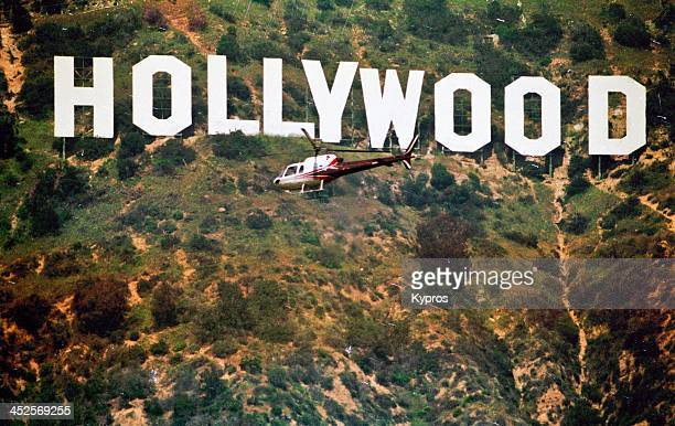 A helicopter in front of the Hollywood sign on Mount Lee in Los Angeles California circa 1990