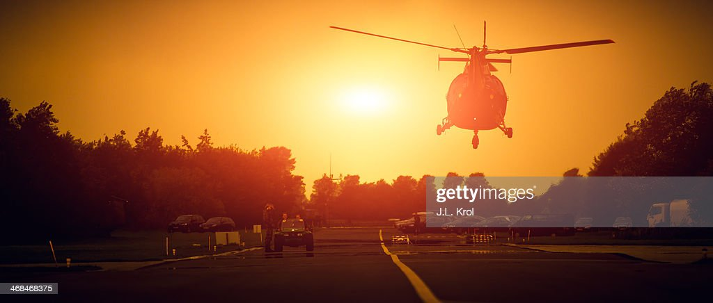 CONTENT] Helicopter in the air, above the road, on a military base in the netherlands. Right in front of a hangar. Vehicle aka Jeep on the road with soldiers watching. Sun is in the air and looks like a war or vietnam movie still scene. Warm picture with mood because of the sunset in the sky.