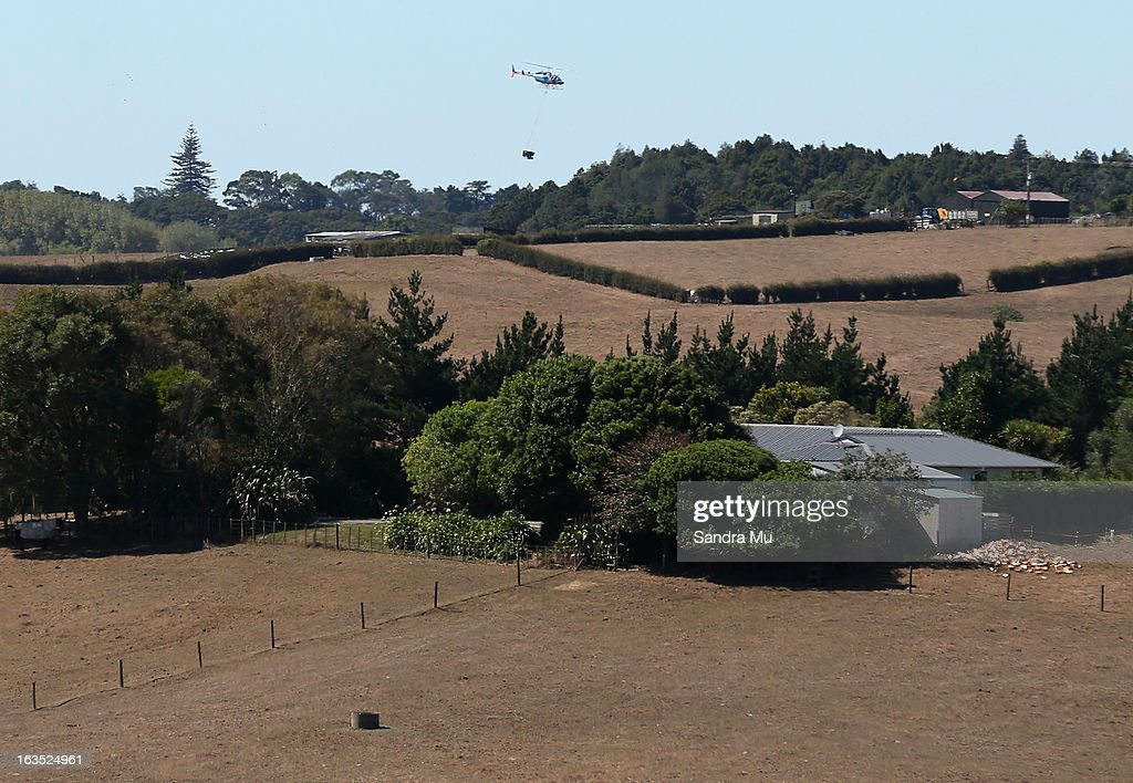 A helicopter is seen with a monsoon bucket flying over drought strickened paddocks on March 12, 2013 in Waiuku, New Zealand. Drought was declared in several North Island areas last week including South Auckland, Northland, Bay of Plenty and Waikato. It is reported by the end of the week the entire North Island will be declared a drought zone.