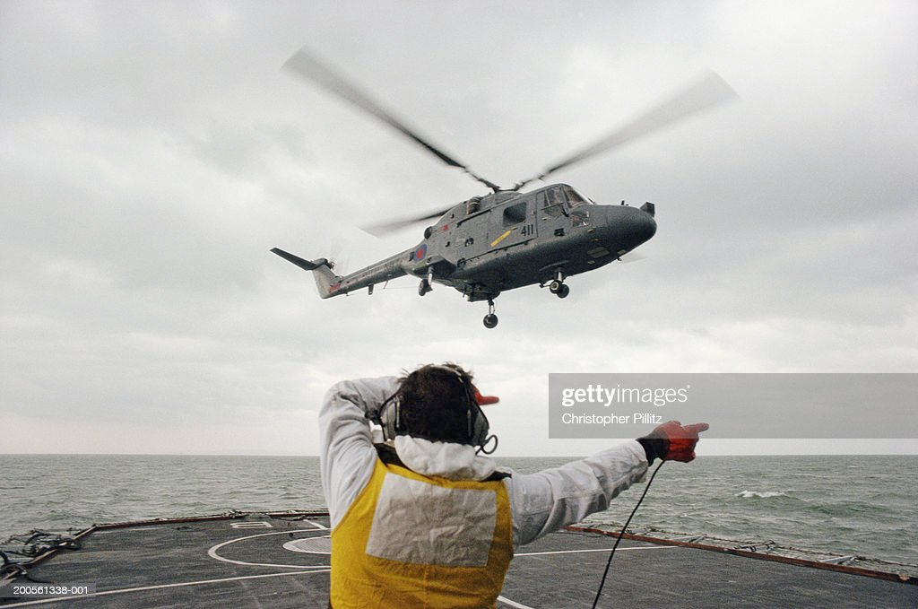 Helicopter lifting off warship, navigator giving directions, rear view