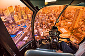Helicopter cockpit inside the cabin flying on Osaka City Central Business downtown at sunset. Osaka Skyline in Japan. Umeda district aerial view.