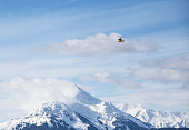 Helicopter over mountain peaks near Haines Alaska transporting heliskiing clients to the mountains.