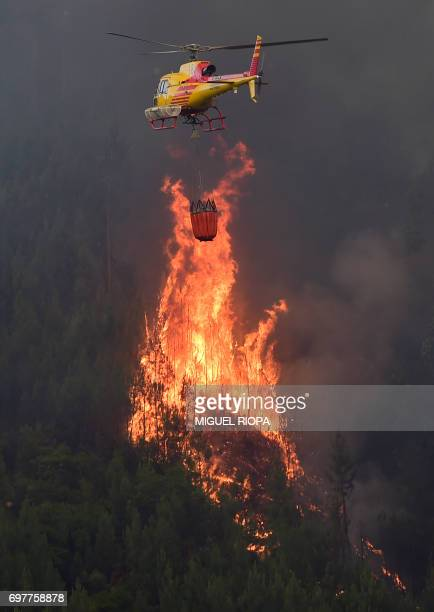 A helicopter overfly a wildfire in Carvalho next to Pampilhosa da Serra on June 19 2017 More than 1000 firefighters are still trying to control the...