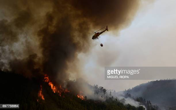 TOPSHOT A helicopter overfly a wildfire in Carvalho next to Pampilhosa da Serra on June 19 2017 More than 1000 firefighters are still trying to...