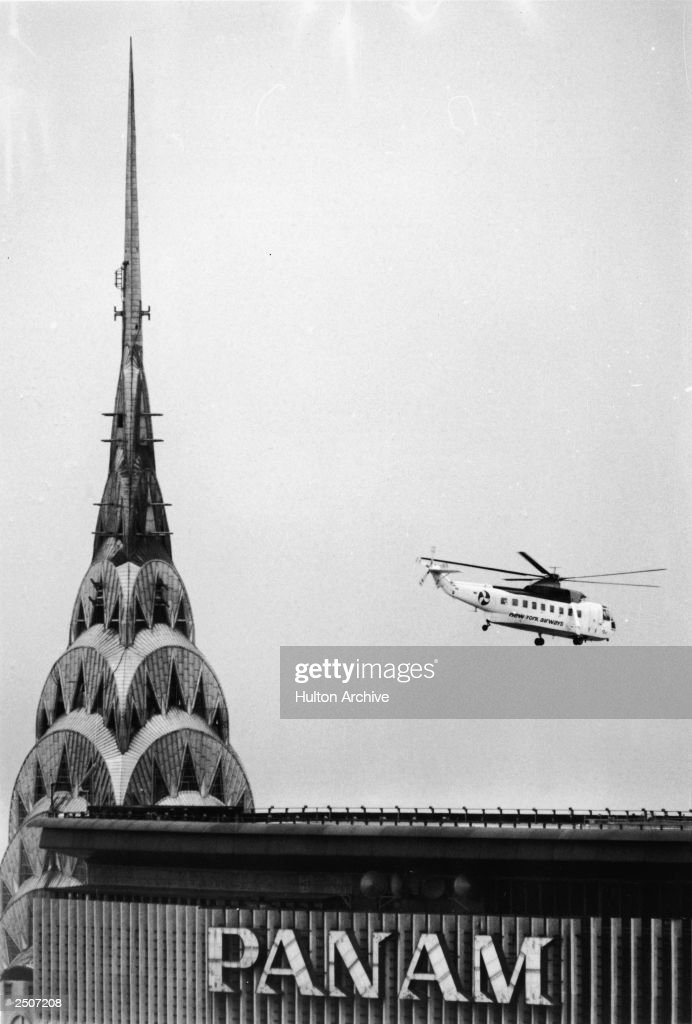 Helicopter passes the art deco spire at the peak of the Chrysler Building, and the Pan Am building, New York City, 1960s.
