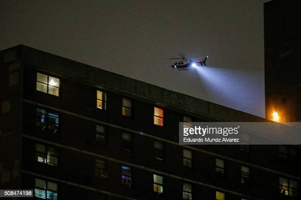 NYPD helicopter patrol over a building after a shooting on February 4 2016 in the Bronx in New York City Two NYPD officers were shot on Thursday...