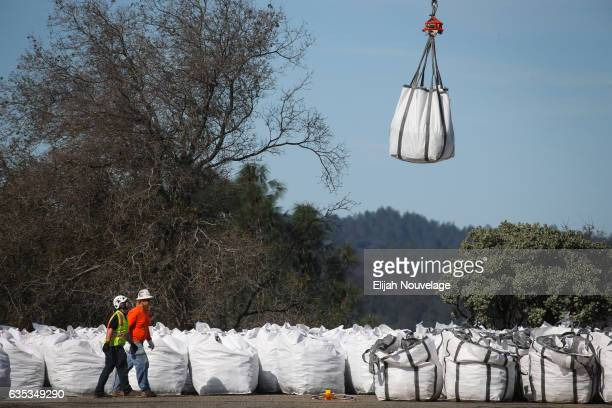 A helicopter picks up a bag of rocks at a staging area near the Oroville Dam on February 14 2017 in Oroville California More than 188000 people were...