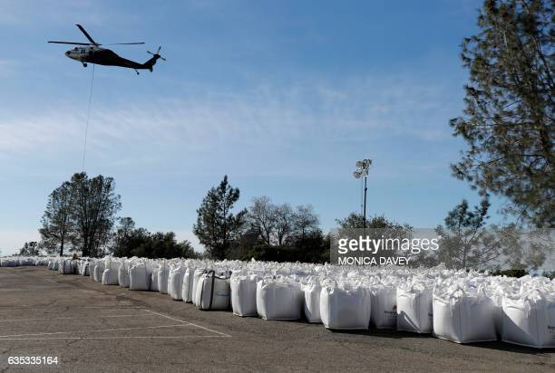 A helicopter picks up rocks to help repair the spillway at the Oroville Dam in Oroville California on February 14 2017 A sheriff lifted a mandatory...