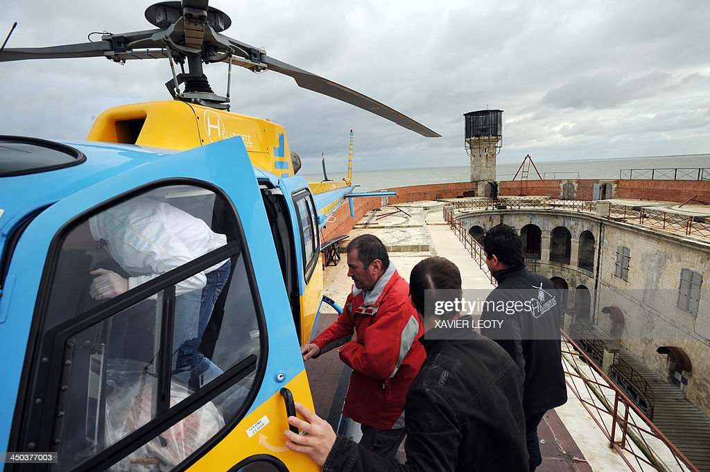 A helicopter picks up workers on Fort Boyard, a fort in the Atlantic Ocean off the coast of France, near La Rochelle, on November 15, 2013. The fort is the filming location for the TV gameshow 'Fort Boyard' and is undergoing renovations. Workers arrive on Monday morning by helicopter and leave on Friday evening. During the winter the renovations are on hold and will pick up again in March 2014.