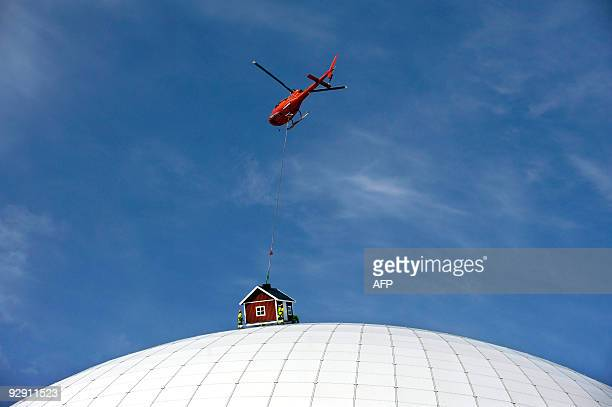 A helicopter places a red cottage designed by Swedish artist Mikael Genberg atop the Ericsson Globe Arena where it will remain for the summer on May...