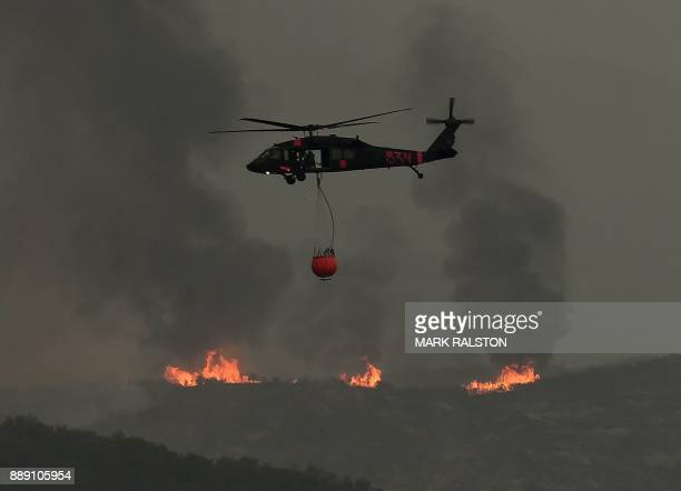 A helicopter prepares to drop water as fire and smoke from the Thomas wildfire heads towards ranches in Ojai California on December 9 2017 Brutal...