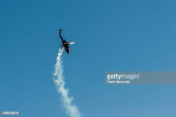ZELTWEG STEIERMARK AUSTRIA A helicopter releasing smoke is performing stunts in the air