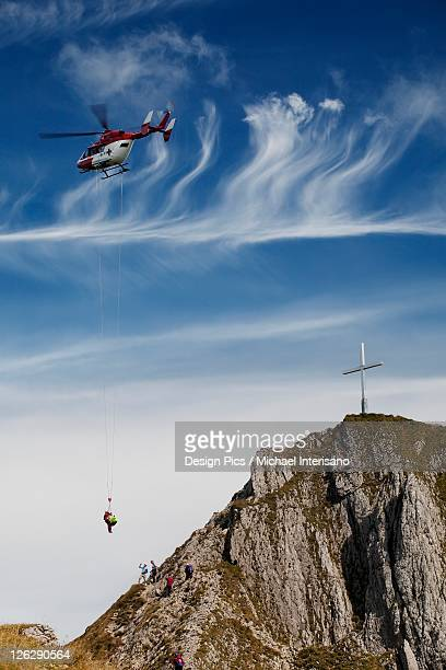 helicopter rescue on a mountain side with a cross on the top of the mountain