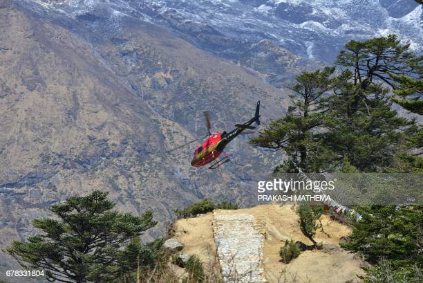 A helicopter takes off from the cremation site of Swiss climber Ueli Steck at Tengboche some 300 kms northeast of Kathmandu on May 4 2017 The body of...