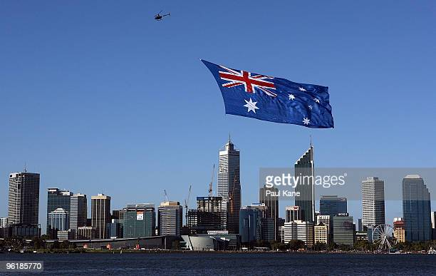 A helicopter tows a large Australian flag past the Perth city skyline prior to the fireworks on the banks of the Swan River as Australia celebrates...