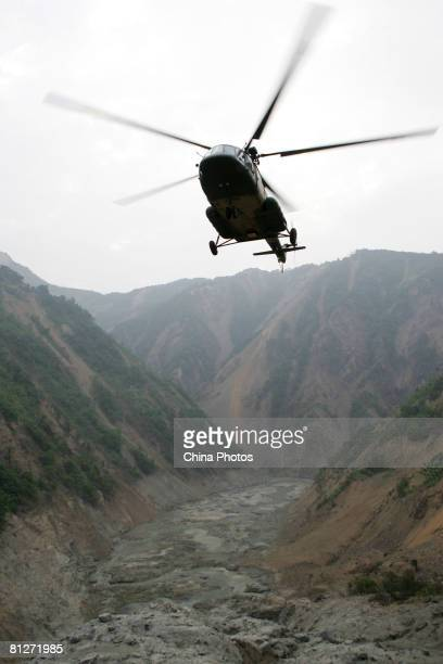 A helicopter transporting goods for the excavation of a channel to drain the Tangjiashan mountain 'quake lake' prepares to land May 28 2008 in...