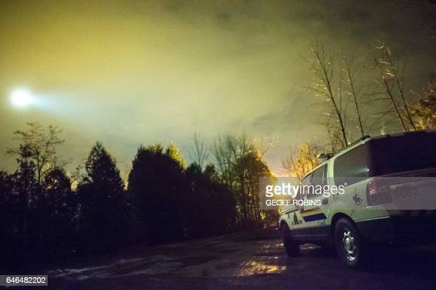 A helicopter with a search light flies over an RCMP vehicle keeping watch over the Canada/US border near Hemmingford Quebec February 28 2017 / AFP /...