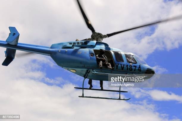 A helicopter with military personnels flies over the military base of the Paramacay Fort in Valencia Venezuela on August 06 2017 Two assailants were...