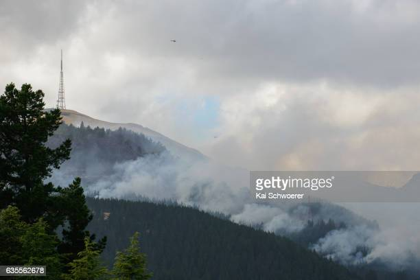 Helicopters are seen as smoke and fire light up between Sugarloaf communications tower and Christchurch Adventure Park on February 16 2017 in...