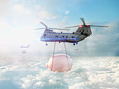 Helicopters carrying piggy banks over clouds