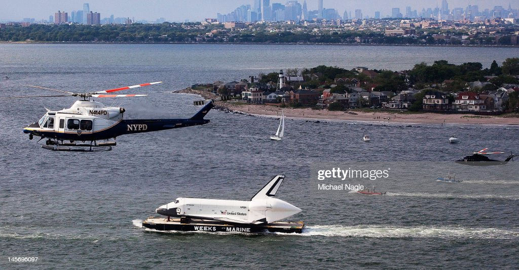 Helicopters fly above Space Shuttle Enterprise, as it's carried by barge past Coney Island, on June 03, 2012 in New York City. Enterprise is on it's way to the Intrepid Sea, Air and Space Museum, where it will put on permanent display.